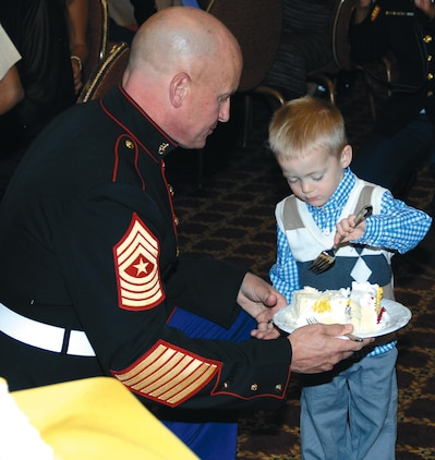 Sgt. Maj. Joseph M. Davenport, sergeant major, Marine Corps Logistics Command, the oldest Marine present at the Kids' Marine Corps Birthday Ball at Marine Corps Logistics Base Albany, passes a slice of cake to the youngest child, Louis Mixa, 2, during a cake-cutting ceremony, Nov. 3. Louis Mixa is the son of Maj. Matthew Mixa, action officer, MCLC. About 150 people attended the first-time event at the Town and Country Restaurant's Grand Ballroom.