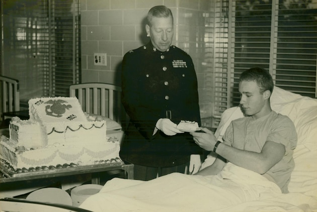 """Although hospitalized Marines were not able to participate actively in the celebration, they did enjoy birthday cake. Colonel F.N. Reeve, Assistant Chief of Staff, G-1, presents a piece of cake to a patient in the U.S. Naval Hospital, Beaufort, South Carolina.""