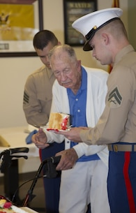 "Cpl. Zachery J. Mehrer, youngest Marine present at age 21, accepts a ceremonial piece of cake from the oldest Marine present, 95-year-old Guy ""Dean"" Smith, during a cake-cutting ceremony observing the Marine Corps' 240th Birthday held at the Veterans Home of California-Barstow, Nov. 4. Mehrer, adjutant clerk for MLCB Barstow, enlisted in the Marine Corps in 2012. Smith enlisted in 1939 and stayed until 1948, then enlisted in the Air Force and completed his military career in 1960."