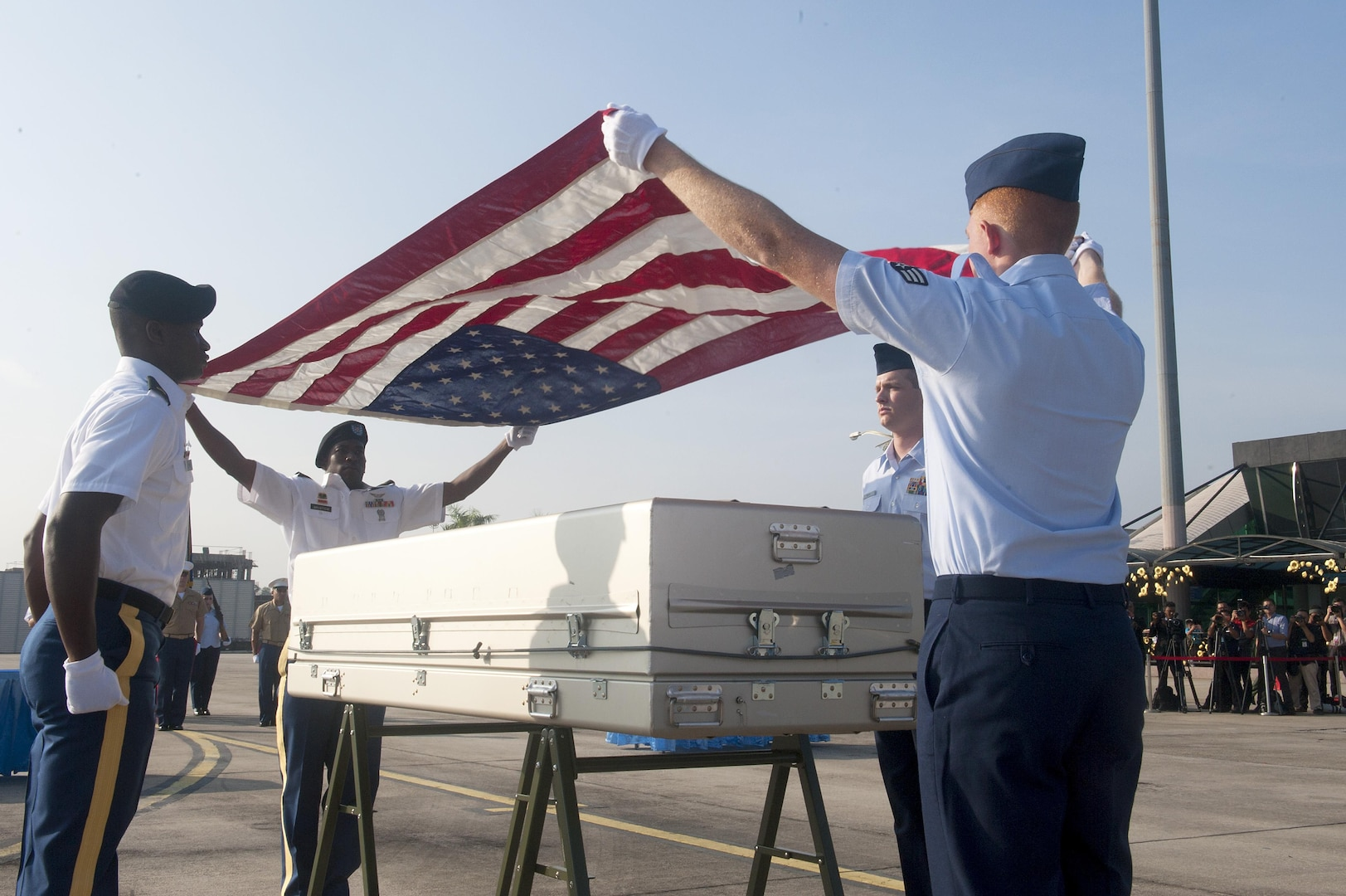 A joint service team drapes an American flag over a casket during a repatriation ceremony at Subang Air Base, Malaysia, Nov. 5, 2015. The 15-member team comprised of members of the Defense POW/MIA Accounting Agency as well service members from United States Army Pacific and Pacific Air Force was sent from Hawaii to honor the remains of a fallen service member who paid the ultimate sacrifice when his plane went down over Malaysia in 1945. The ceremony signifies the transfer of the remains from Malaysia back to the U.S. where the service member can be returned home. The ceremony marks the first of its kind between the two countries. The mission of the Defense POW/MIA Accounting Agency is to provide the fullest possible accounting for our missing personnel to their families and the nation. (U.S. Air Force photo by Staff Sgt. Brian J. Valencia)
