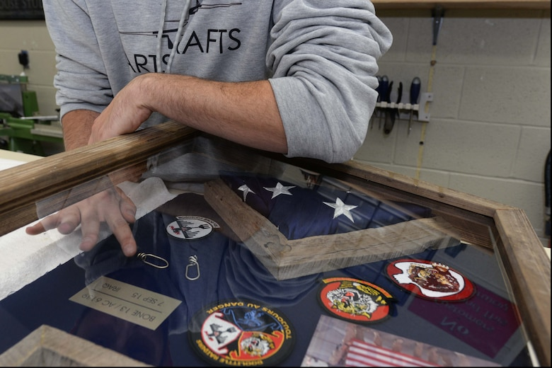 Joe Altergott, 28th Force Support Squadron visual information specialist, puts the finishing touches on a shadowbox at Ellsworth Air Force Base, S.D., Oct. 30, 2015. The box included an American flag, among other items, was presented to retired Lt. Col. Dick Cole, one of two surviving Doolittle Raiders, as a way to express Ellsworth's gratitude and appreciation to him and all Tokyo Raiders. (U.S. Air Force photo by Senior Airman Rebecca Imwalle/Released)