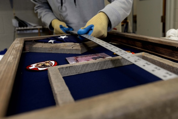 Joe Altergott, 28th Force Support Squadron visual information specialist, measures the height of a shadowbox at Ellsworth Air Force Base, S.D., Oct. 23, 2015. The box contains items flown by the 37th Bomb Squadron during missions in support of Operation Inherent Resolve on the 100th birthday of retired Lt. Col. Dick Cole, one of two surviving Doolittle Raiders. (U.S. Air Force photo by Senior Airman Rebecca Imwalle/Released)