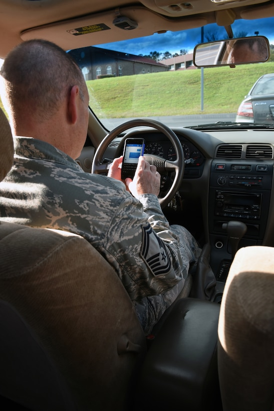 MCGHEE TYSON AIR NATIONAL GUARD BASE, Tenn. - Senior Master Sgt. Paul Mann sends a text message in his car here Nov. 4, 2015, while parked. Service members cannot use a cell phone, except for hands-free, when driving on base.  Texting and driving is illegal. You cannot use your cell phone in any way if you are driving a government vehicle, no matter where you are. State laws vary too, so officials recommend you learn them. (U.S. Air National Guard photo by Master Sgt. Mike R. Smith/Released)