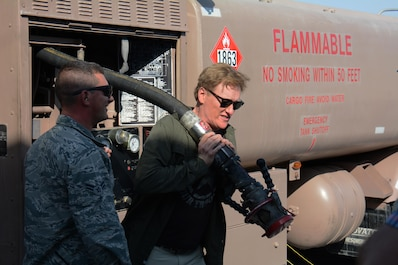 Late night talk show host and comedian, Conan O'Brien, attempts to haul a fuel line to an RC-135 Stratotanker at Al Udeid Air Base, Qatar Nov. 4 during a base visit. O'Brien visited AUAB to meet with and entertain service members. He said he was honored to spend time with America's warriors and thanked all service members for what they do to defend America's freedom. (U.S. Air Force photo by Tech. Sgt. James Hodgman)