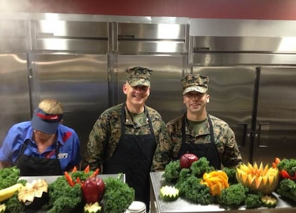 On November 6, 2015 Lieutenant Colonel Taylor P. White and Captain Zack A. Pinkerton, officers with Marine Corps Engineer School (MCES), assist Sodexo employees in serving the Marine Corps' birthday meal at Courthouse Bay, Camp Lejeune, N.C.