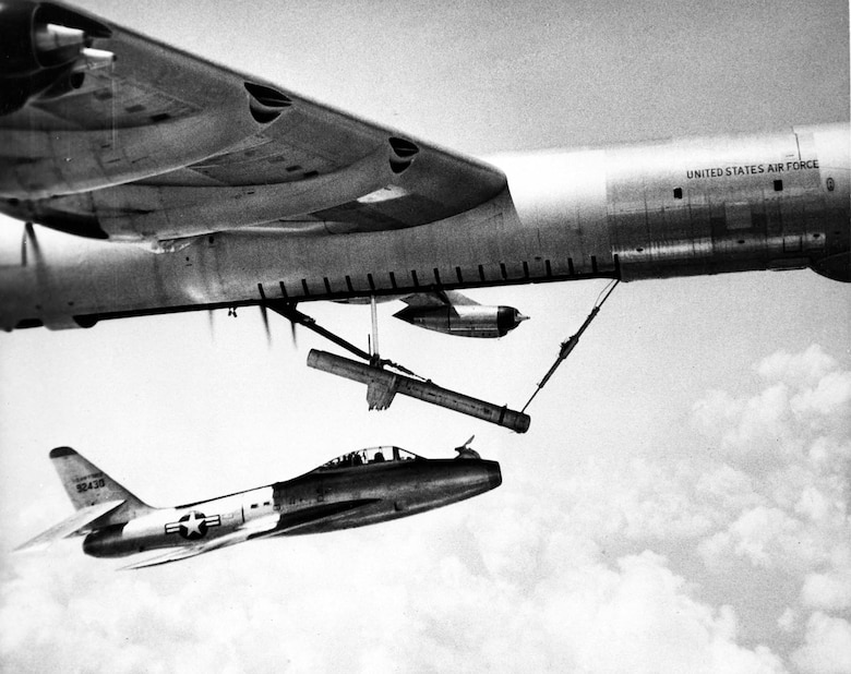 The YRF-84F flying underneath its B-36 carrier aircraft. FICON modifications included installing a hook in front of the cockpit and turning down the horizontal tail so it could partially fit into the B-36 bomb bay. (U.S. Air Force photo)