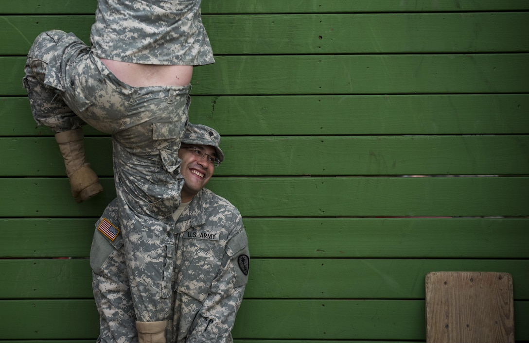Spc. Josue Centeno, a U.S. Army Reserve Soldier with the 354th Military Police Company, of St. Louis, Mo., lifts a Soldier up a wall as they navigate through a Leadership Reaction Course as part of a team-building exercise at Camp Atterbury, Ind., Nov. 5, during a three-day range training event hosted and organized by the 384th Military Police Battalion, headquartered at Fort Wayne, Ind. The field training involving more than 550 U.S. Army Reserve Soldiers and included ranges using eight different weapons systems, plus combat patrolling and a rifle marskmanship competition. (U.S. Army photo by Master Sgt. Michel Sauret)