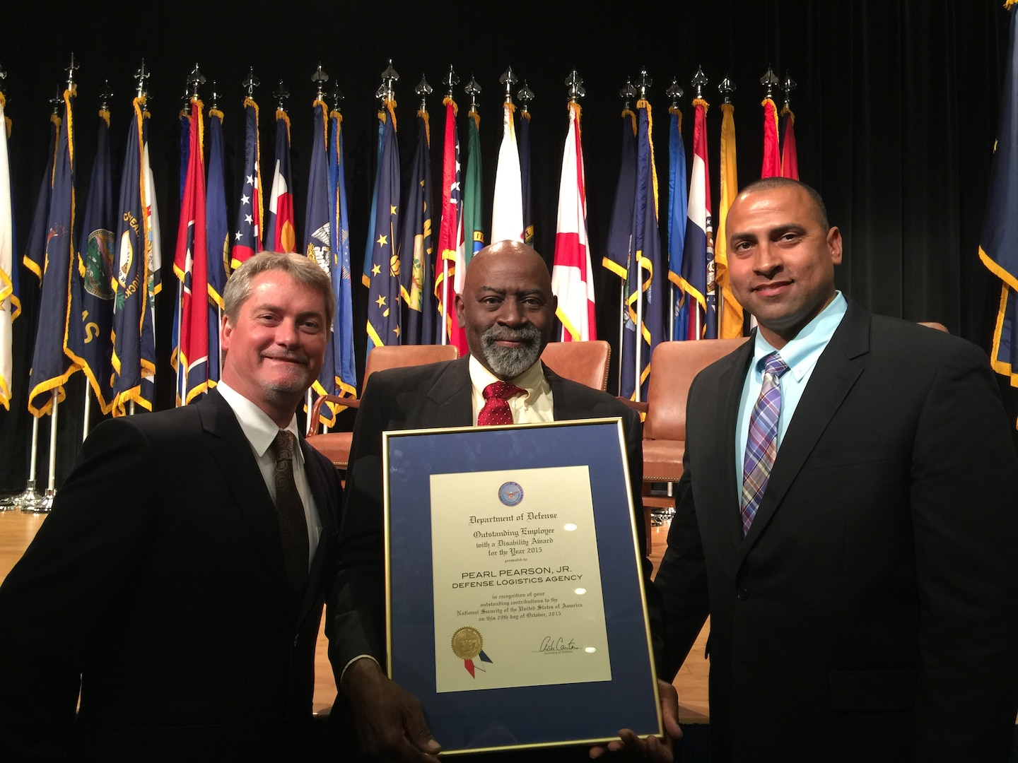 Terry Phillips and Dack Pearson, Pearl Pearson's son, pose with Pearson at the 35th annual Department of Defense Disability Awards ceremony held in the Pentagon Auditorium on Oct. 29.