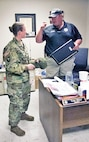 Lt. Col. Jennifer A. Reynolds, commander, 3rd AHB, 1st Avn. Regt., 1st CAB, 1st Inf. Div., presents Wolf with a baseball cap with her battalion's logo Sept. 22.