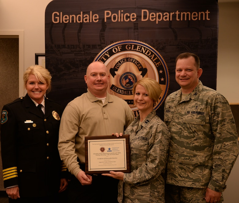 Debora Black, Glendale Chief of Police, Sgt. Patrick Beumler, Glendale Criminal Investigations Officer, Capt. Sonja Raciti, Luke Family Advocacy Officer, and Col. Stephen Boden, commander of the 56th Medical Operations Squadron, pose with an International Association of Chiefs of Police award Nov. 5, at the Glendale Family Advocacy Center. The award was presented to both the Glendale Police Department and the Luke FAC in honor of their joint efforts to support and protect victims of domestic violence and abuse. (U.S. Air Force photo by Airman 1st Class Ridge Shan)