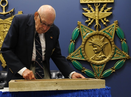 Retired Lt. Col. Dick Cole, one of two surviving Doolittle Raiders, admires a shadowbox presented to him at the Pentagon, Arlington, Va., Nov. 5, 2015. Cole was the co-pilot of the first B-25 to launch off the deck of the USS Hornet with Lt. Col. James Doolittle during the Doolittle Raid in 1942. (U.S. Air Force photo by Staff Sgt. Carlin Leslie/Released)