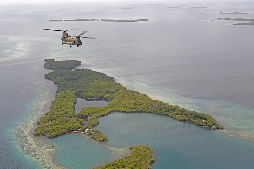 A U.S. Army CH-47 Chinook helicopter flies over the coast of Belize, Oct. 25, 2015 en route to a drug eradication mission with Belizean security forces. The Chinook and its aircrew provided a means for the eradication teams to access various areas in the country to help combat illegal trafficking and cultivation of narcotics. (U.S. Air Force photo by Senior Airman Westin Warburton/Released)
