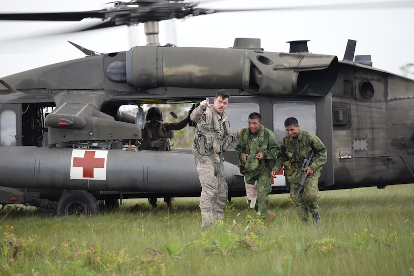 U.S. Army Staff Sgt. Zach Lattimore, 1-228 Aviation Regiment flight medic, gives directions to Belizean security forces during a mock medical evacuation mission, Oct. 26, 2015, in Belize. The mock mission was part of the training the Belizean security forces and U.S. Army conducted prior to a four-day long drug eradication mission. (U.S. Air Force photo by Senior Airman Westin Warburton/Released)