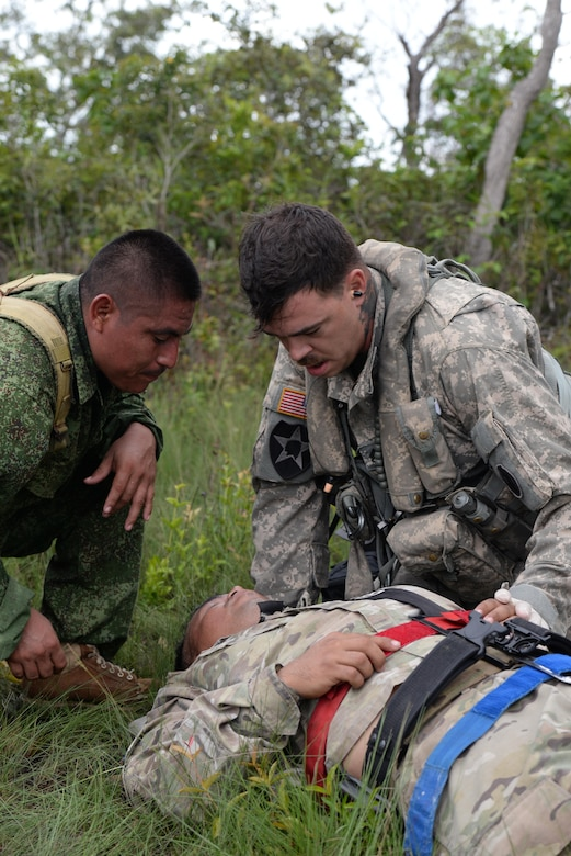 U.S. Army Staff Sgt. Zach Lattimore, 1-228 Aviation Regiment flight medic, treats a simulated patient alongside a Belize Defense Force member during a mock medical evacuation mission Oct. 26, 2015, in Belize. The training prepared the teams for any potential scenario that may have required a medical evacuation during a four-day drug eradication operation. (U.S. Air Force photo by Senior Airman Westin Warburton/Released)
