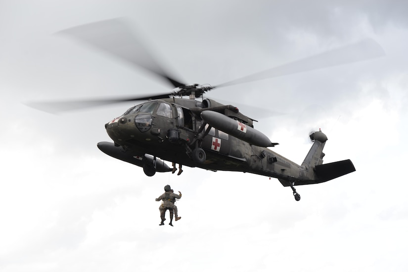 U.S. Army Staff Sgt. Zach Lattimore, 1-228 Aviation Regiment flight medic, and a Belize Defense Force member are hoisted into a UH-60 Blackhawk helicopter during a mock medical evacuation mission, Oct. 26, 2015, in Belize. The U.S. Army provided airlift capabilities to the Belizean forces during an operation to eradicate marijuana fields throughout Belize, which was proceeded by training missions to familiarize the Belizeans with the U.S. aircraft and techniques. (U.S. Air Force photo by Senior Airman Westin Warburton/Released)