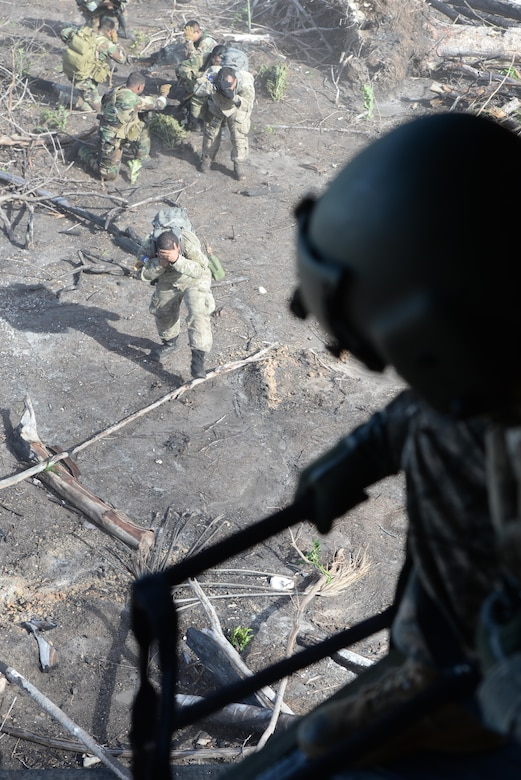 U.S. Army Sgt. Dane Rogge, 1-228 Aviation Regiment crew chief, drops a ladder from a CH-47 Chinook helicopter for Belizean forces to climb during a marijuana eradication mission, Oct. 27, 2015 in Belize. The four-day operation with the Belizean security forces and U.S. Army resulted in the eradication of over 50,000 marijuana plants and put the Belize forces at the head of the intelligence efforts for the operation with U.S. airlift supporting the effort. (U.S. Air Force photo by Senior Airman Westin Warburton/Released)