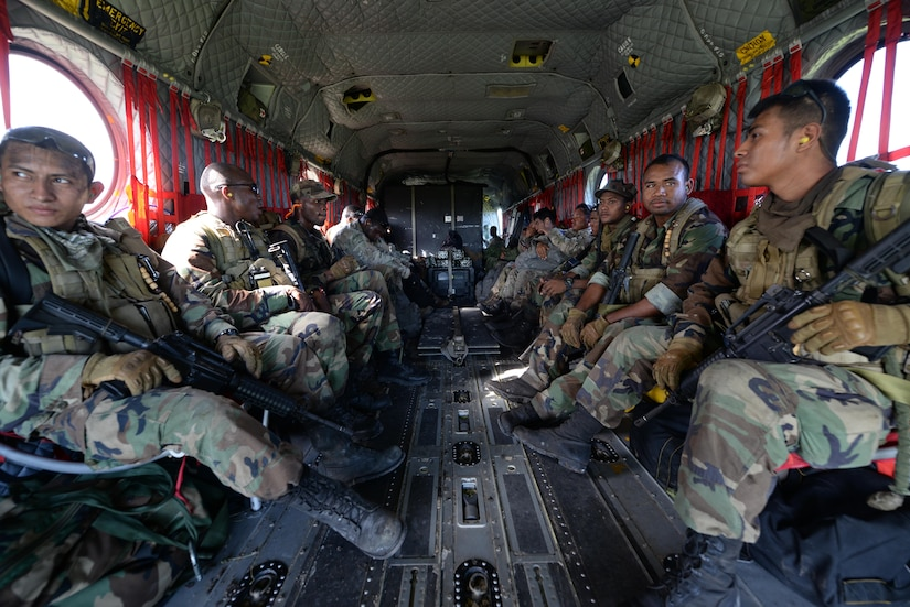 Belizean security forces members ride aboard a U.S. Army CH-47 Chinook helicopter during a marijuana eradication mission, Oct. 27, 2015, in Belize. The U.S. Army provided airlift capabilities to the Belizean security forces during the eradication of marijuana fields identified by Belizean Intelligence throughout the four-day operation. (U.S. Air Force photo by Senior Airman Westin Warburton/Released)