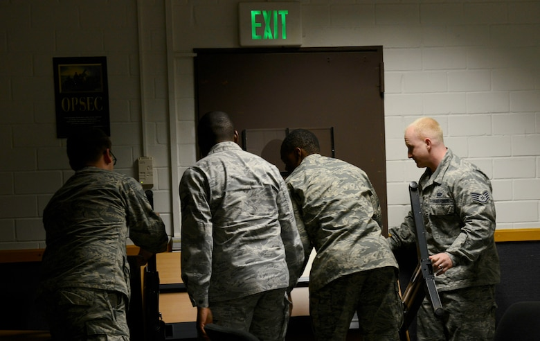 Students in the Expeditionary Active Shooter Training class barricade a door during a simulated active shooter scenario Nov. 5, 2015, at Ramstein Air Base, Germany. The E.A.S.T. class is a requirement for deploying Airmen and includes hands-on practical training to further prepare the student for a real active shooter situation. (U.S. Air Force photo/Airman 1st Class Tryphena Mayhugh)
