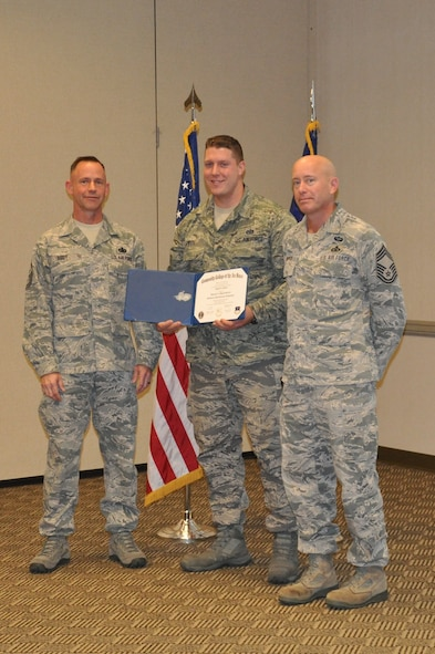 Chiefs VanPate and Eddy are on hand as TSgt Justin Smith is awarded his Associate's Degree from Community College of the Air Force.( U.S Air National Guard photo by SSgt. Holly Wohlford/ Released)