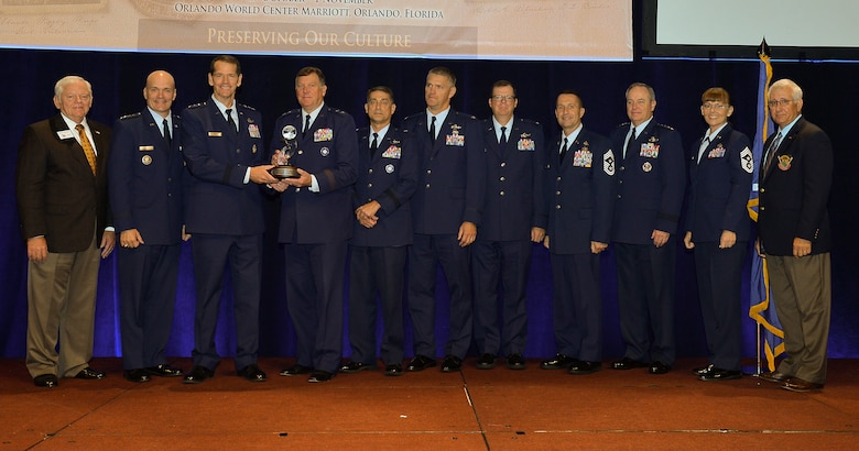 The director of the Air National Guard, Lt. Gen. Stanley Clarke III (third from left) presents Maj. Gen. Edward Tonini (fourth from left), adjutant general of the Commonwealth of Kentucky, with the 2015 Airlift/Tanker Association's Major General Stanley F.H. Newman Outstanding Unit Award during the annual A/TA Convention in Orlando, Fla., Oct. 30, 2015. The award was bestowed this year on the Kentucky Air National Guard's 123rd Airlift Wing, based in Louisville, for exceptional performance from July 1, 2014 to June 30, 2015. Also pictured (left to eight) are Gen. Arthur Lichte (retired), chairman of the A/TA; Gen. Carlton Everhart II, commander of Air Mobility Command; Brig. Gen. Warren Hurst, Kentucky's assistant adjutant general for Air; Col. Barry Gorter, commander of the 123rd Airlift Wing; Col. Robert Hamm, commander of the 123rd Operations Group; Chief Master Sgt. Ray Dawson, command chief of the 123rd Airlift Wing; Gen. Mark Welsh III, chief of staff of the U.S. Air Force; Chief Master Sgt. Victoria Gamble, command chief of Air Mobility Command; and Lt. Gen. Christopher Kelly (retired), former vice commander of Air Mobility Command. (U.S. Air Force photo).