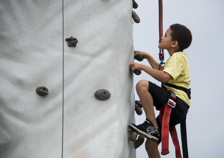 A kid climbs the rock wall during the Duke Field Wing Day event Nov. 7.  The 919th Special Operations Wing sets aside a special day each year to show appreciation for its reservists and their family members. Events included music, sports, children's games, etc. (U.S. Air Force photo/Tech. Sgt. Cheryl Foster)