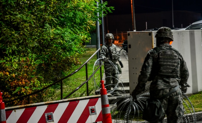Security forces members from the 51st Fighter Wing lay out concertina wire around a strategic point on Osan Air Base, Republic of Korea, Nov. 2, 2015, during Vigilant Ace 16. The razor laden wire is used during exercises to help cordon off areas from foot and light vehicle traffic. More than 16,000 U.S. personnel will participate in Vigilant Ace 16, an exercise designed to enhance interoperability between U.S. and Republic of Korea forces and increase the combat effectiveness of both nations. (U.S. Air Force photo/Tech. Sgt. Travis Edwards)