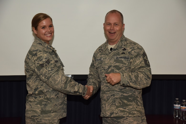SIOUX FALLS, S.D. - Command Chief Master Sergeant of the Air National Guard James W. Hotaling presents his coin to Senior Airman Katherine Johnston, 114th Operations Group airfield management operations specialist, during his visit to the 114th Fighter Wing, Sioux Falls, S.D.,Nov. 7, 2015. The ANG's senior enlisted advisor presented eight members of the 114th with his coin to recognize outstanding Airmen from the unit. (U.S. Air National Guard photo by Staff Sgt. Luke Olson/Released)