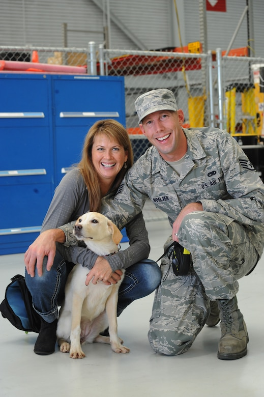 Oregon Air National Guard Staff Sgt. Joshua Boelter along with his wife Sara, pause for a photograph with Luna, a Romania puppy rescued during deployment and reunited, Nov. 5, 2015, Portland Air National Guard Base, Ore. (U.S. Air National Guard photo by Tech. Sgt. John Hughel, 142nd Fighter Wing Public Affairs/Released)