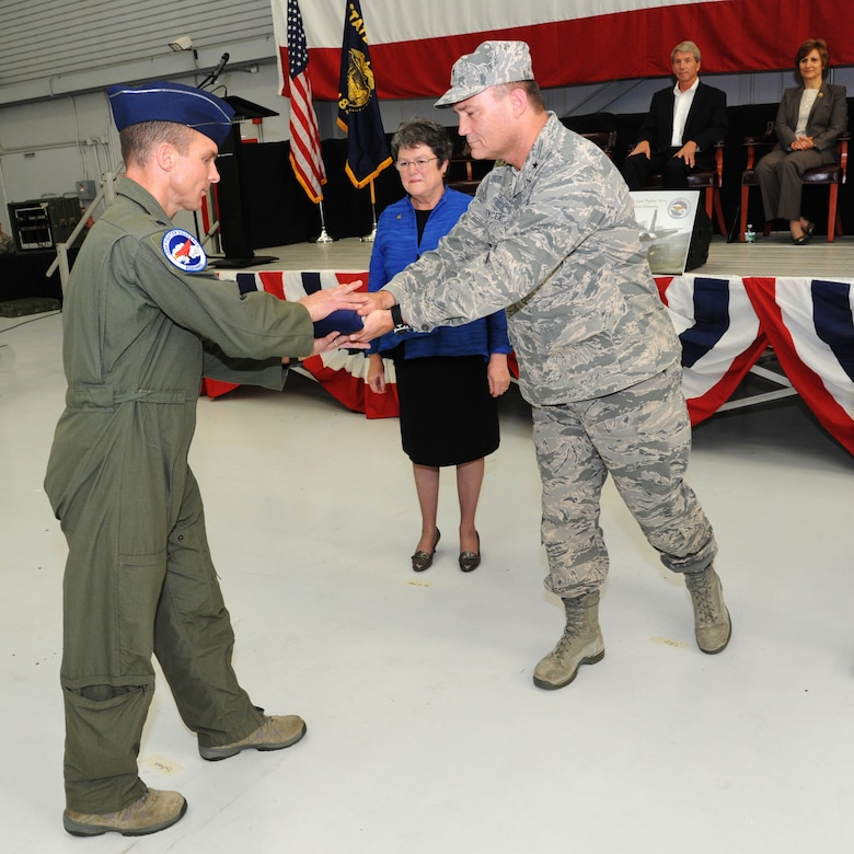 Lt. Col. Sean Sullivan, 123rd Expeditionary Fighter Squadron commander, left, exchanges the state flag of Oregon with Brig. Gen. Michael E. Stencel, Adjutant General, Oregon, during the formal demobilization ceremony, Nov. 6, 2015, Portland Air National Guard Base, Ore. (U.S. Air National Guard photo by Tech. Sgt. John Hughel, 142nd Fighter Wing Public Affairs/Released)