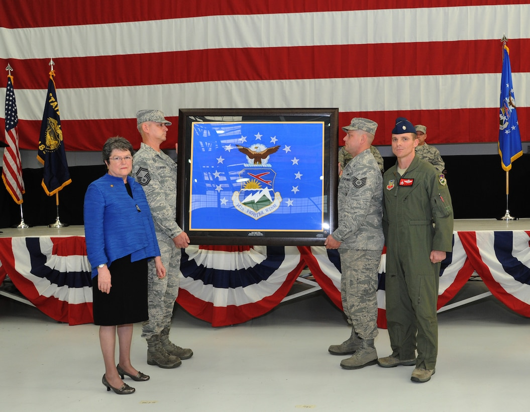 Oregon Secretary of State Jeanne Atkins, left, stands with Lt. Col. Sean Sullivan, 123rd Fighter Squadron commander, right, as the unit flag for the 142nd Fighter Wing is presented during the demobilization ceremony for the 123rd Expeditionary Fighter Squadron, 142nd Fighter Wing, Nov. 6, 2015, Portland Air National Guard Base, Ore. (U.S. Air National Guard photo by Tech. Sgt. John Hughel, 142nd Fighter Wing Public Affairs/Released)