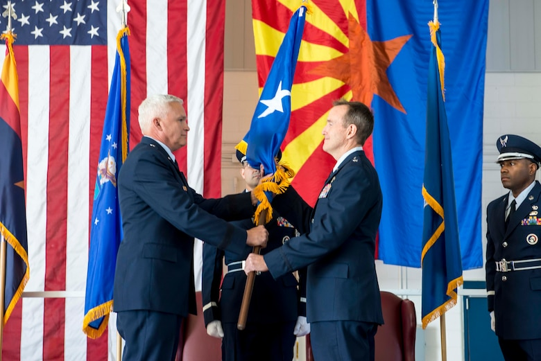 "TUCSON, Ariz. -- The commander of the Arizona Air National Guard, Brig. Gen. Edward P. Maxwell, left, symbolically recognizes the presence of a new general by passing the customary one-star brigadier general flag to newly-promoted Brig. Gen. Howard P. Purcell, 162nd Wing Commander. ""No matter what my rank, being a part of your team is the job of a lifetime,"" said Purcell. ""I am extremely proud to be your commander and can't thank you enough."" (U.S. Air National Guard photo by Tech. Sgt. Hollie A. Hansen /Released)"