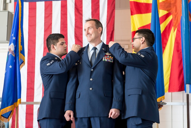 TUCSON, Ariz. – Airman 1st Class Ricardo Badilla, left, and Airman 1st Class Edwin Martinez, right, pin silver stars on newly-promoted Brig. Gen. Howard P. Purcell, 162nd Wing Commander, Nov. 7 at the 162 Wing at the Tucson International Airport. Breaking from tradition, Purcell chose the most junior enlisted Airmen from each group to perform the honor of pinning on the service dress jacket's silver stars and placing new shoulder boards for his dress shirt – embodying a commitment to his own Air National Guard family. (U.S. Air National Guard photo by Tech. Sgt. Hollie A. Hansen /Released)