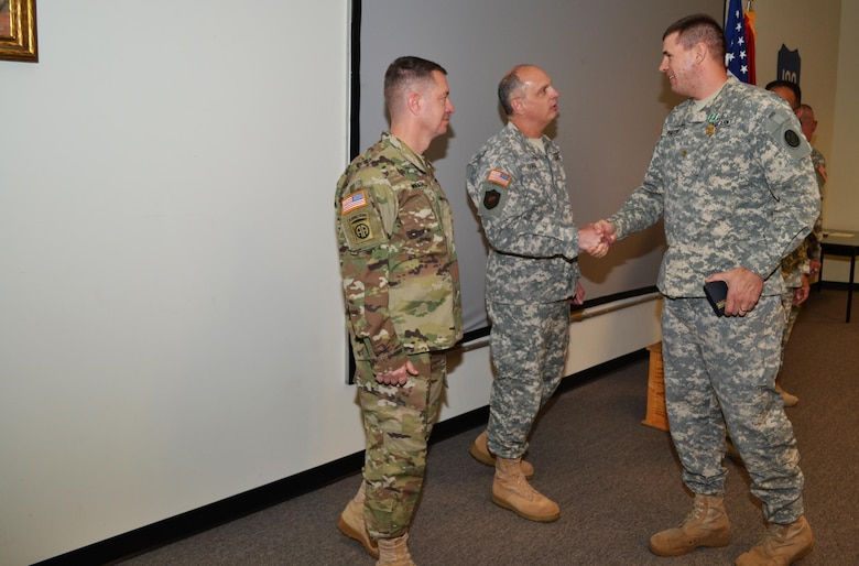 Brig. Gen. Jason Walrath, commander 100th Training Division, looks on as Brig. Gen. Brig. Gen. Thomas P. Evans, deputy commander 80th Training Command, congratulates the 80th TC Instructor Of the Year in the officer category, Maj. David Porter, 102d Training Division, during an award ceremony at Fort Knox, Ky., Nov. 7, 2015.