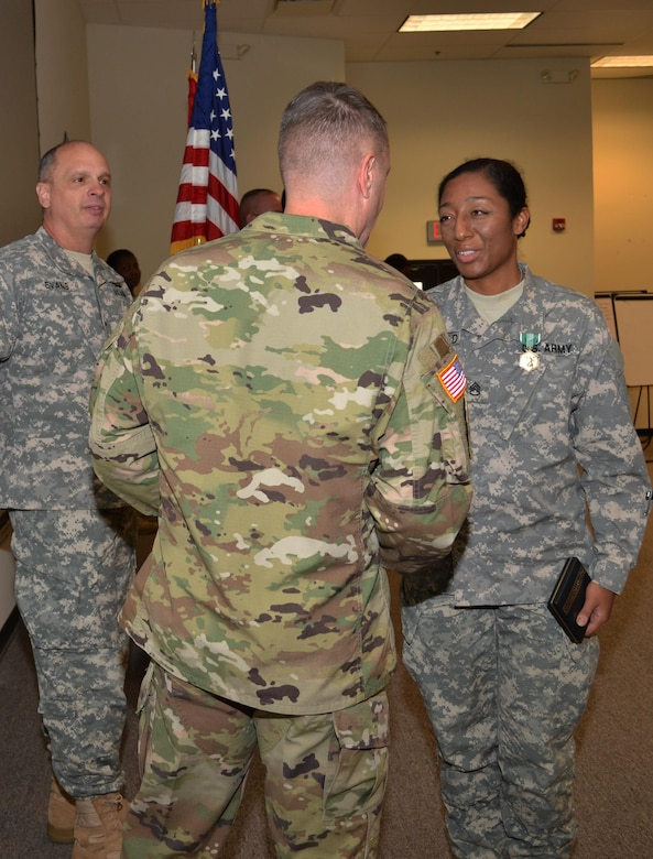 Brig. Gen. Thomas P. Evans, deputy commander 80th Training Command, looks on as Brig. Gen. Jason Walrath, commander 100th Training Division, congratulates the 80th TC Instructor Of the Year in the noncommissioned officer category, Staff Sgt. Jadrian Whitfield, 100th TD, during an award ceremony at Fort Knox, Ky., Nov. 7, 2015.