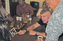 Maj. Gen. Wayne W. Grigsby, Jr., commanding general of the 1st Infantry Division and Fort Riley, converses with Amanda Doster, a Gold Star Family member, during a small informal lunch.  Grigsby is pointing to a photo of Amanda's late husband, SFC James Doster, who was killed in action in Iraq on Sept. 29, 2007.