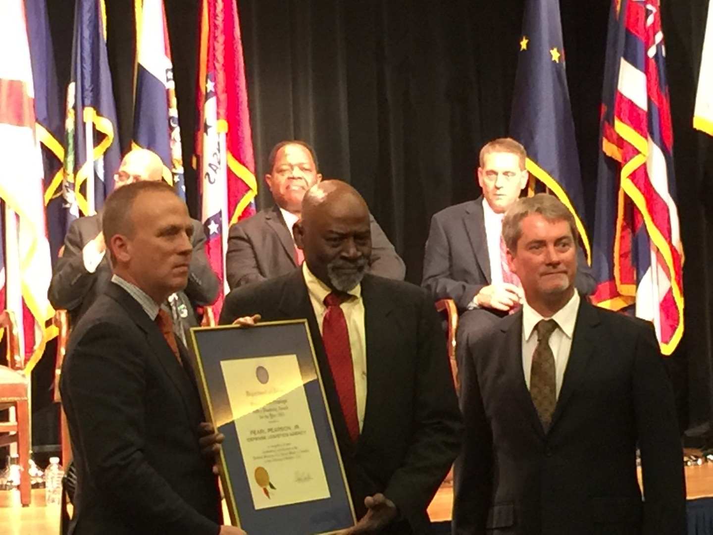 Pearl Pearson, Jr., (center), was presented with the 2015 Outstanding DoD Employee with a Disability Award by Brad R. Carson, (left) Undersecretary of Defense for Personnel and Readiness, and Terry Phillips, (right) Preservation, Packaging, Packing and Marking Branch Chief at the 35th annual Department of Defense Disability Awards ceremony held in the Pentagon Auditorium on Oct. 29.