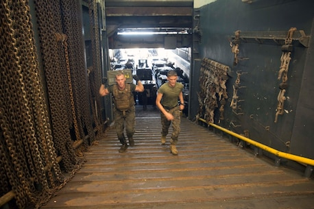 GULF OF ADEN (Oct. 17, 2015) U.S Marine Cpl. Shawn Obrien, left, sprints with an ammo can during the combat conditioning portion of a Marine Corps Martial Arts Program black belt course aboard the USS Rushmore (LSD 47). Obrien is an amphibious assault vehicle crew chief with Kilo Company, Battalion Landing Team 3rd Battalion, 1st Marine Regiment, 15th Marine Expeditionary Unit. In In addition enhancing hand-to-hand combat skills, MCMAP sharpens the decision making and mental toughness of the Marines by instilling a warrior ethos.. (U.S. Marine Corps photo by Sgt. Emmanuel Ramos/Released)