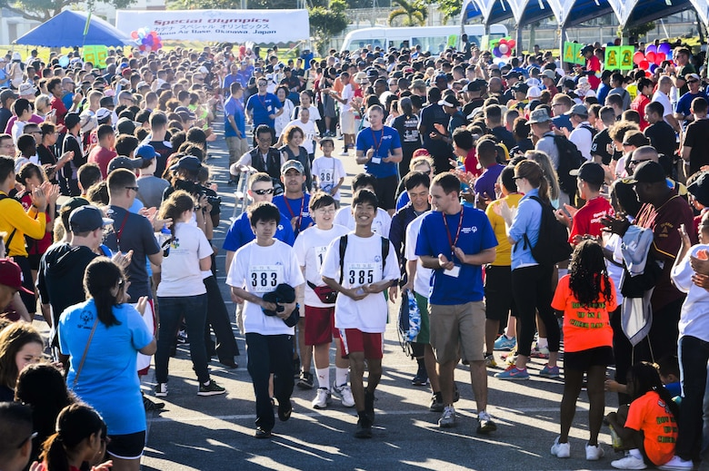 Hundreds of volunteers and spectators of the Kadena Special Olympics form a human pathway to greet and cheer on arriving athletes as they are shuttled to the Risner Fitness Center Sports Complex Nov. 7, 2015, at Kadena Air Base, Japan. Thousands of spectators from Japan and the U.S. came out to support approximately 880 athletes and artists participating in the 16th annual KSO games and art show. (U.S. Air Force photo by Senior Airman John Linzmeier/Released)