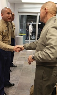 Commandant of the Marine Corps, Gen. Robert B. Neller, presents Gunnery Sgt. Andrew Francisco, staff noncommissioned officer of Recruiting Sub Station Granada Hills, with his challenge coin, Nov. 6, 2015, after winning SNCOIC of the year for the Western Region. The commandant flew in to Los Angeles to attend the Reagan National Defense Forum, and upon landing at the Camarillo airport, he recognized the Marines for their hard work and dedication in recruiting efforts. (U.S. Marine Corps photo by Sgt. Alicia R. Leaders/Released)