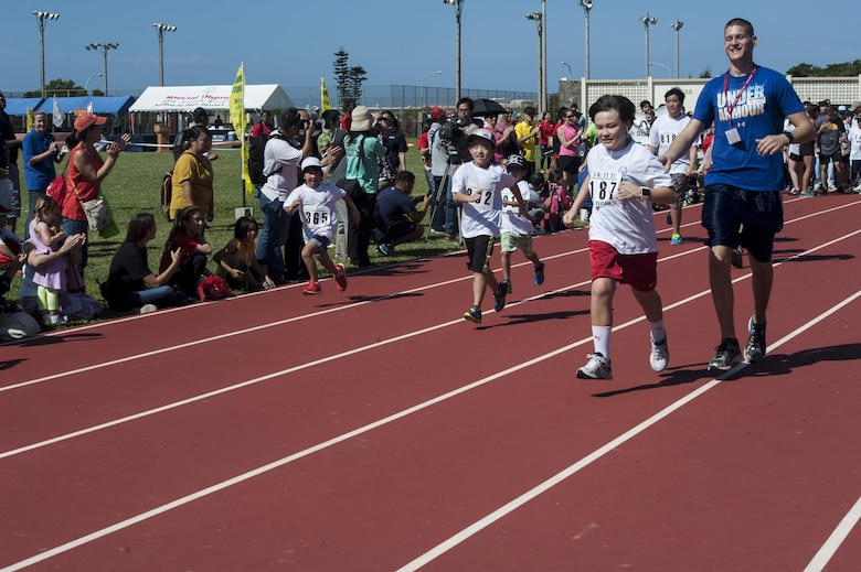 U.S. Air Force Airman 1st Class Anthony Sojka, 18th Component Maintenance Squadron aerospace propulsion apprentice, runs with Teisan Scarborough, a Kadena Special Olympics athlete, during the Kadena Special Olympics Nov. 7, 2015, at Kadena Air Base, Japan. Approximately 1700 volunteers helped nearly 900 athletes arrive to their events and compete in the largest overseas Special Olympics in the world. (U.S. Air Force photo by Airman 1st Class Lynette M. Rolen/Released)