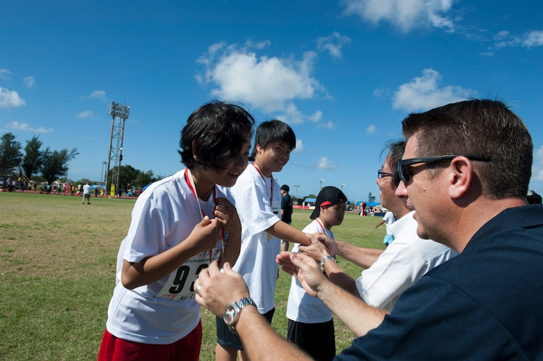 U.S. Air Force Col. Christopher Amrhein, 18th Wing vice commander, gives a medal to Mirai Tamanaha, a Kadena Special Olympics athlete, during the Kadena Special Olympics Nov. 7, 2015, at Kadena Air Base, Japan. The KSO is a one-day sporting, art and entertainment event with more than 880 athletes and artists participating in a day of competition, music and special recognition. (U.S. Air Force photo by Airman 1st Class Lynette M. Rolen/Released)