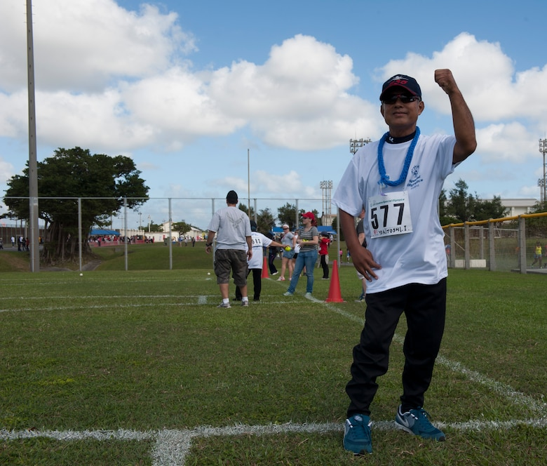 Yukitoshi Iriishigaki, a Kadena Special Olympics athlete, cheers after throwing a softball during the Kadena Special Olympics Nov. 7, 2015, at Kadena Air Base, Japan. KSO is a non-profit activity managed by volunteers from around the island and funded by donations as a goodwill initiative to give back to those with special needs. (U.S. Air Force photo by Airman 1st Class Lynette M. Rolen/Relased)