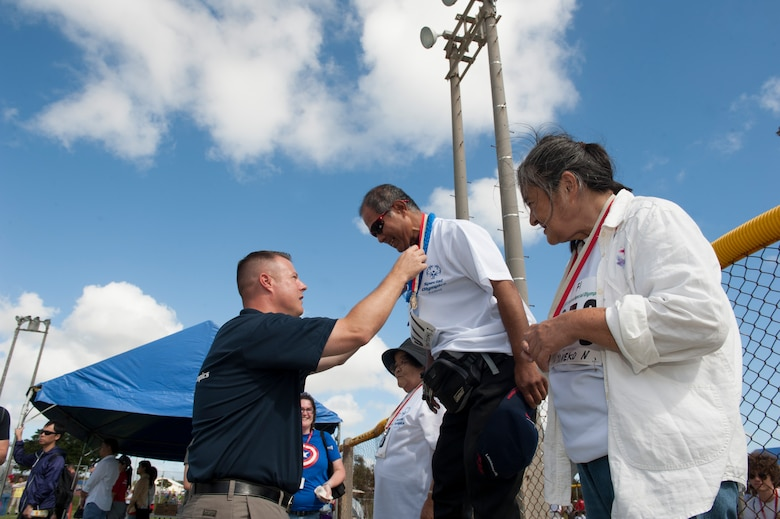 U.S. Air Force Chief Master Sgt. Charles Hoffman, 18th Wing command chief master sergeant, presents a medal to Yukitoshi Iriishigaki, a Kadena Special Olympics athlete, for winning first place in the softball skills tournament during the Kadena Special Olympics Nov. 7, 2015, at Kadena Air Base, Japan. KSO was established by the 18th Wing commander in 2000 as an avenue to build relations with the local communities and government representatives while providing a meaningful activity for members of the special needs community on Okinawa. (U.S. Air Force photo by Airman 1st Class Lynette M. Rolen/Released)