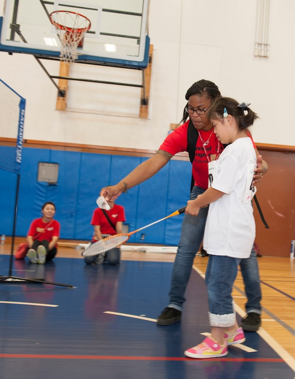 U.S. Air Force Airman 1st Class Amiya Jones, 18th Security Forces Squadron armorer, helps Yuri Yonaha, a Kadena Special Olympics athlete, with her badminton skills during the Kadena Special Olympics Nov. 7, 2015, at Kadena Air Base, Japan. This year marks the 16th anniversary of KSO, a sporting event dedicated to enriching the lives of American and Okinawan special needs individuals on the island. (U.S. Air Force photo by Airman 1st Class Lynette M. Rolen/Released)
