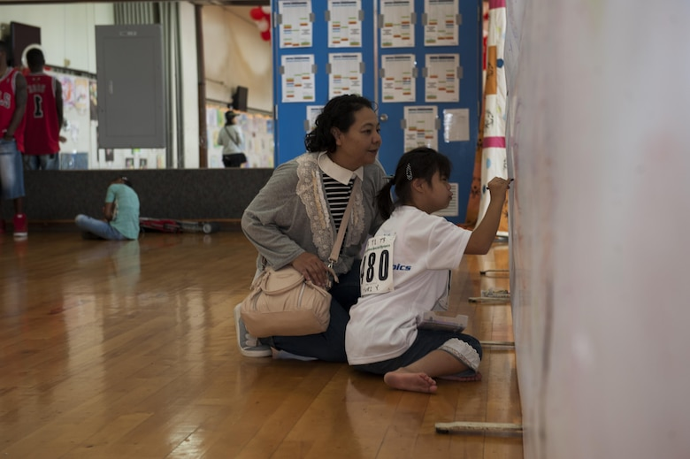 Yuri Yonaha, a Kadena Special Olympics athlete, draws on a canvas while her mother observes at the art exhibit during the Kadena Special Olympics Nov. 7, 2015, at Kadena Air Base, Japan. Thousands of spectators from Japan and the U.S. came out to support approximately 880 athletes and artists participating in the 16th annual KSO games and art show. (U.S. Air Force photo by Airman 1st Class Lynette M. Rolen/Released)