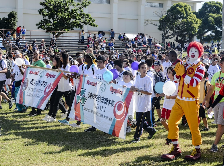 Participants and volunteers of the Kadena Special Olympics parade down the Risner Fitness Center field during the event's opening ceremony Nov. 7, 2015, at Kadena Air Base, Japan. KSO is a non-profit activity managed by volunteers from around the island and funded by donations as a goodwill initiative to give back to those with special needs. (U.S. Air Force photo by Senior Airman John Linzmeier/Released)