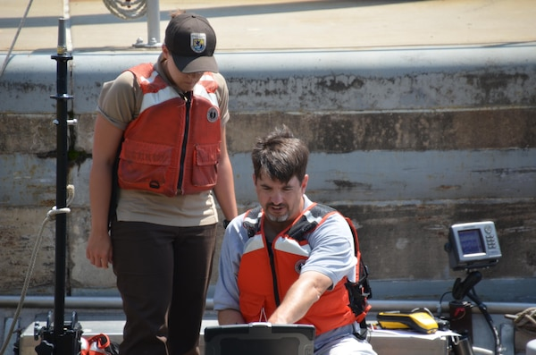 Elliot Stefanik, sitting, fish biologist, explains to Jenna Merry, U.S Fish and Wildlife Service student, how the hydro-acoustic camera will help researches better understand fish behavior within the Mississippi River.