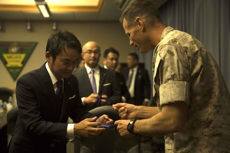 Daisuke Haneshiro, left, exchanges business cards with Lt. Col. James J. Hurd during a visit and educational tour October 14 on Marine Corps Air Station Futenma. During the visit, chairmen of the Japan-Russia Friendship Association were instructed on the history and tenant units of MCAS Futenma. After a question and answer session, Marine officials provided the chairmen with a windshield tour of the air station. Haneshiro is a chairman with the Japan-Russia Friendship Association. Hurd is the executive officer of MCAS Futenma, Marine Corps Installations Pacific and a Kingston, New Hampshire, native.