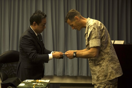 Masaoki Fukui, left, exchanges business cards with Lt. Col. James J. Hurd during a visit and educational tour October 14 on Marine Corps Air Station Futenma. During the visit, chairmen of the Japan-Russia Friendship Association were informed about the history and tenant units of MCAS Futenma and their capabilities. After a question and answer session, the guests boarded a bus for a windshield tour of the installation. Fukui is a chairman with the Japan-Russia Friendship Association. Hurd is the executive officer of MCAS Futenma, Marine Corps Installations Pacific and a Kingston, New Hampshire, native.
