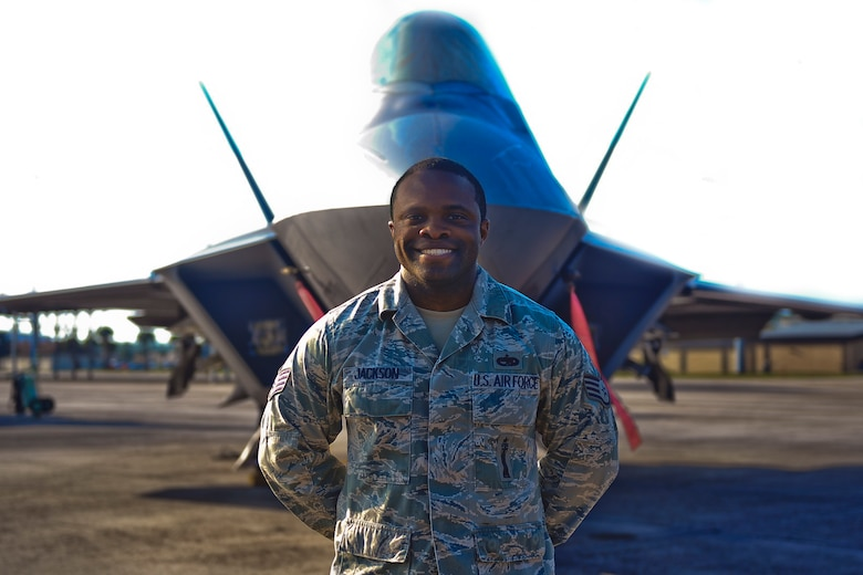 Staff Sgt. Cheyenne Jackson, 325th Aircraft Maintenance Squadron weapons load crew chief, stands in front of an F-22 Raptor Nov. 11 on the Tyndall flightline. Jackson was selected to be the 325th AMXS unsung hero for his significant contributions to the squadron. (U.S. Air Force photo by Senior Airman Dustin Mullen/Released)